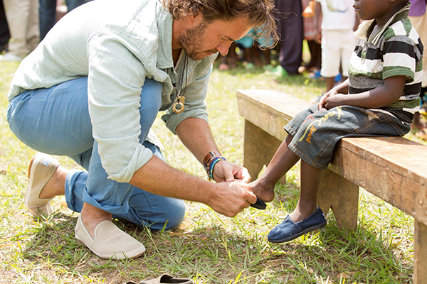 TOMS Founder, Blake Mycoskie Giving shoes to a child in need