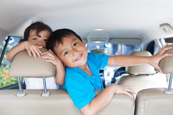 Smiling happy siblings playful in the car