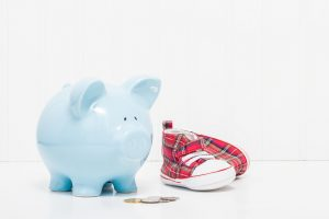 Porcelain piggy bank and baby shoes. Portrays the concept of starting to save early in life.