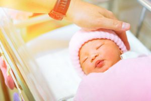 father hand touching sleeping infant head with pink hat