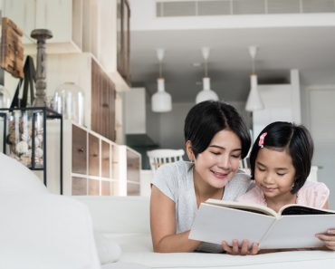 Asian mother and daughter reading a book at home.