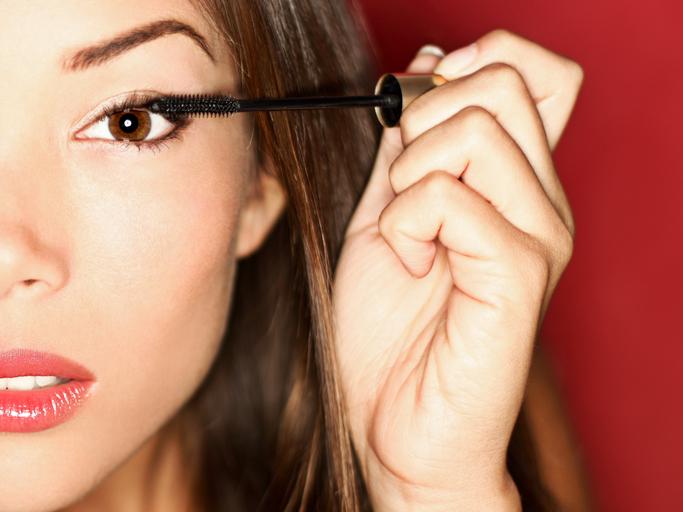 Woman putting mascara makeup