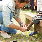 TOMS-Founder-Blake-Mycoskie-Giving-shoes-to-a-child-in-need1 RP