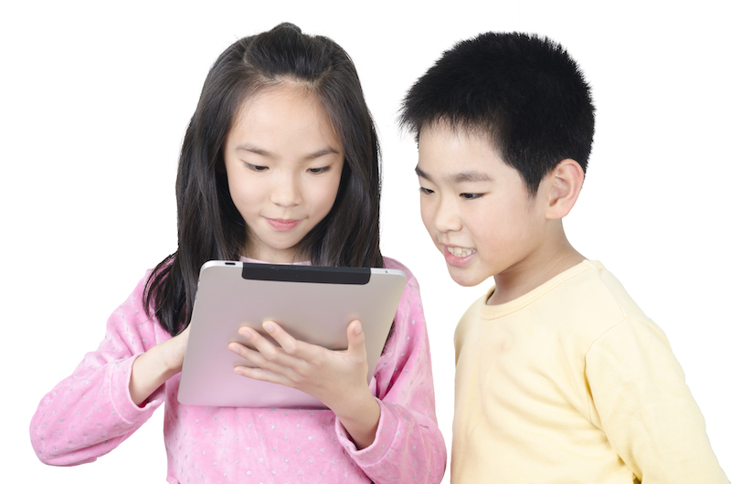 two happy children using tablet computer and isolated on white