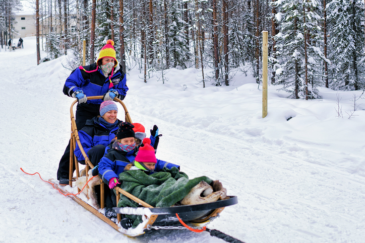Family with children riding husky dogs sledge in Lapland
