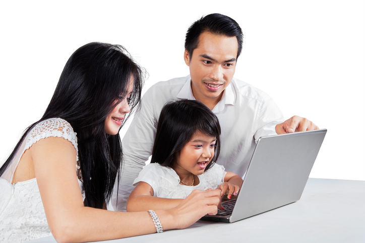 Happy parents using laptop with their child